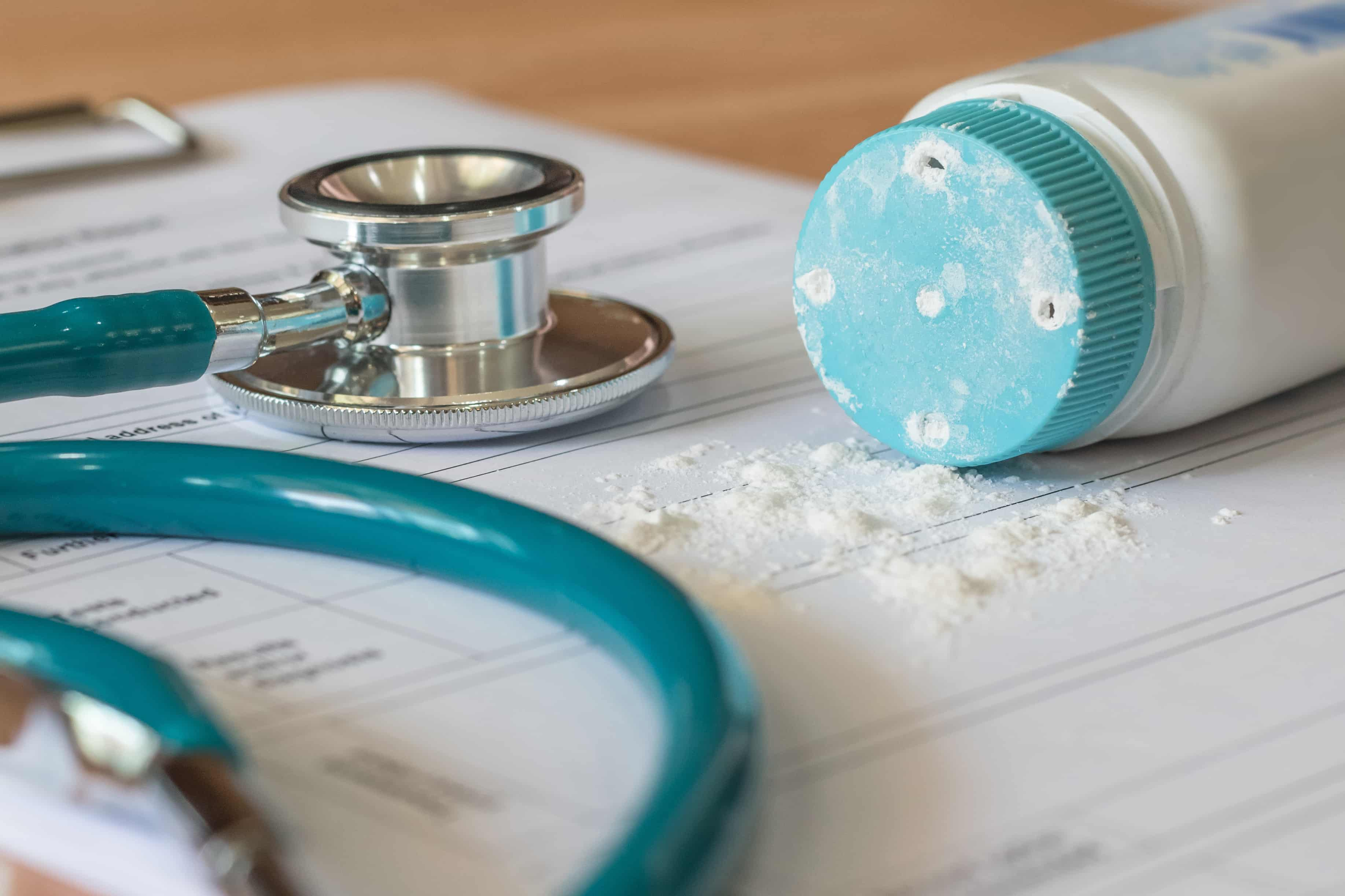 Image of spilled talcum powder from an unmarked talcum powder bottle next to a stethoscope